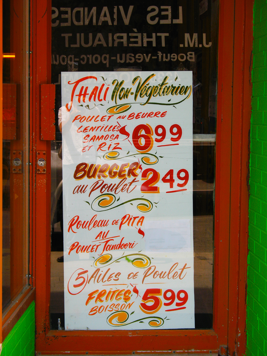 photo of a doorway with a sandwich board promoting thali, burgers, pita sandwiches, and chicken wings in French