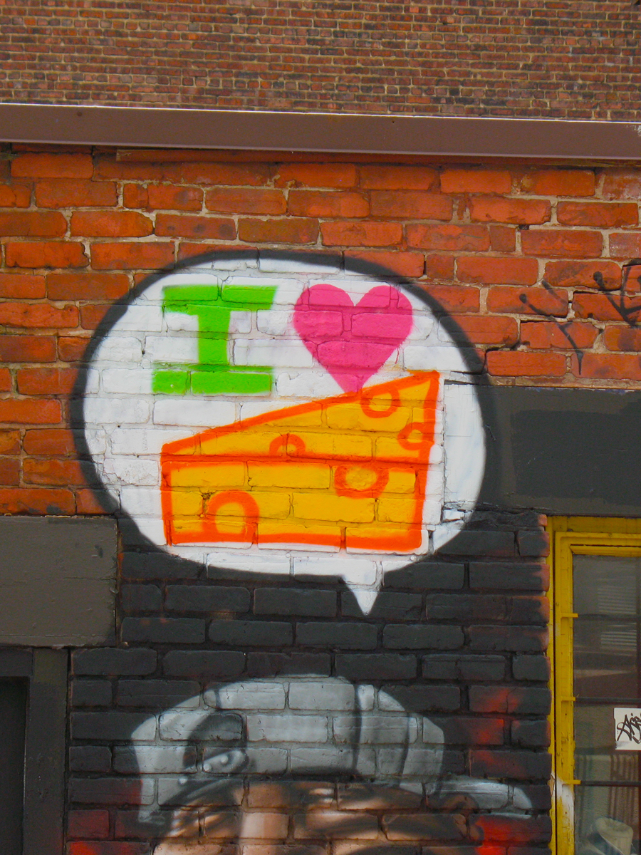 """photograph of urban graffiti on a city wall showing a thought bubble saying """"I love cheese"""" in graphic elements"""