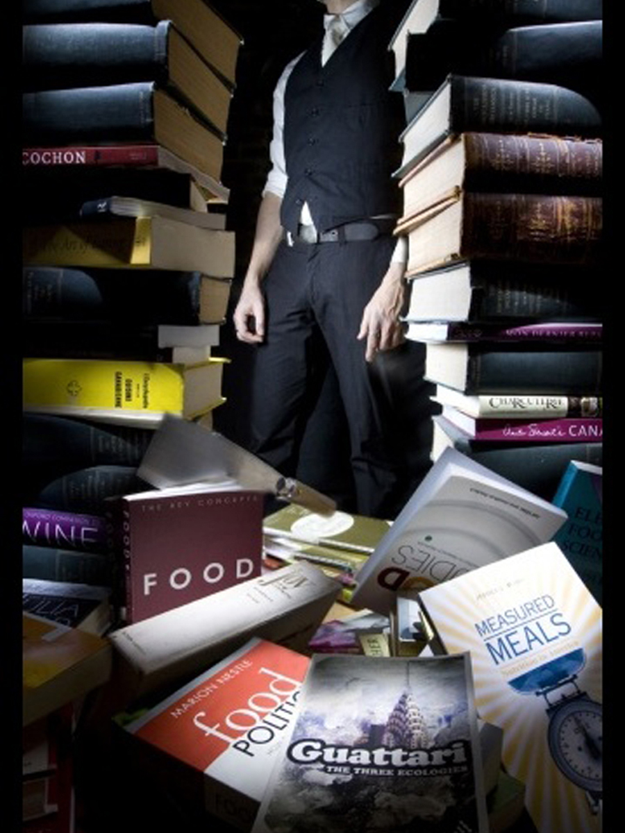 photo of a figure standing behind a pile of food books, one of which has a cleaver in it